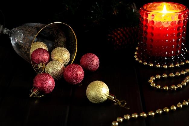 Weihnachtskomposition mit einer glaskerze und glitzerkugeln