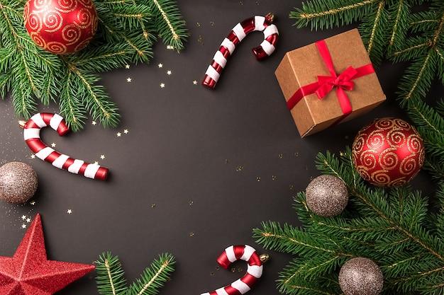 Weihnachtskomposition mit fichtenzweigen und weihnachtsschmuck auf schwarzem hintergrund