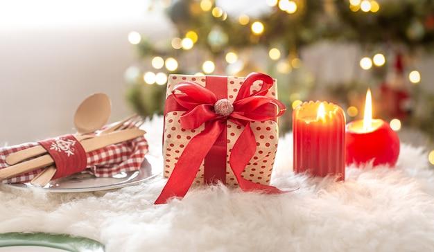 Weihnachtskomposition mit geschenkbox, kerzen und ornamenten