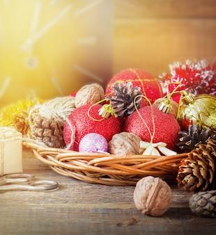 Weihnachtskomposition mit geschenken. korb, rote bälle, tannenzapfen, schneeflocken auf holztisch. vintage-stil