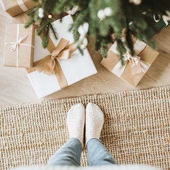 Weihnachtskomposition mit handgefertigten geschenkboxen, firtree-zweigen und frauenfüßen. draufsicht, flatlay
