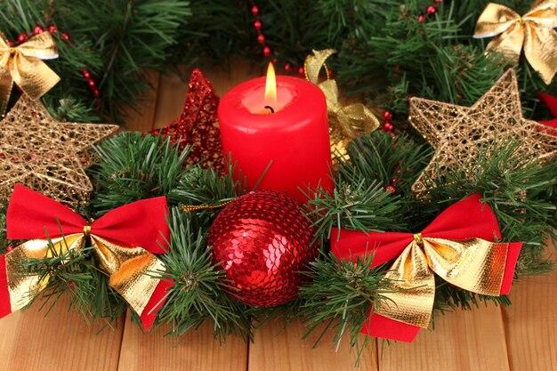 Weihnachtskomposition mit kerze und dekorationen in rot- und goldfarben auf holztisch
