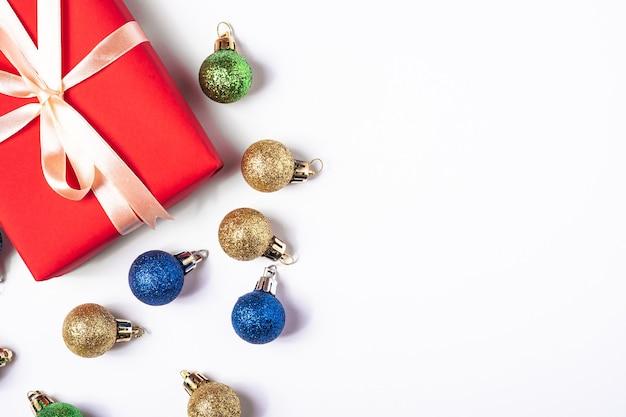 Weihnachtskomposition mit kopierraum. bunte kugeln, geschenkbox und verzierungen dekorationen auf weißem hintergrund
