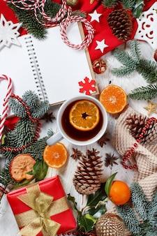 Weihnachtskomposition mit notizbuch, teetasse und geschenkbox