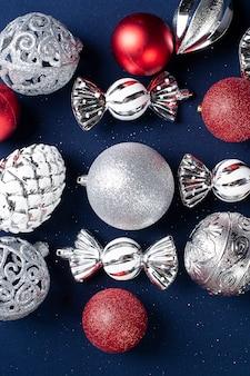 Weihnachtskomposition mit roten und silbernen ornamenten auf blau