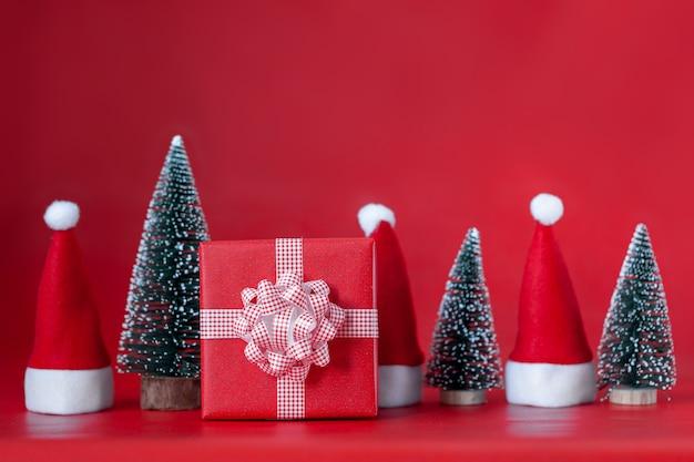 Weihnachtskomposition mit roter geschenkbox und weihnachtsbaum und weihnachtsmützen auf rot