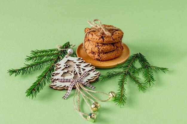 Weihnachtskomposition mit schokoladenkeksen auf grünem papier mit tannenzweigen und holzspielzeug. festliche grußkarte.