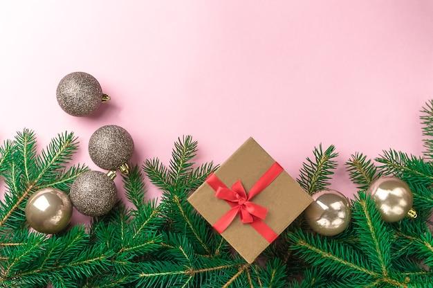 Weihnachtskomposition mit silbernen weihnachtskugeln, tannenzweigen und geschenkbox mit bürokratie auf rosa hintergrund