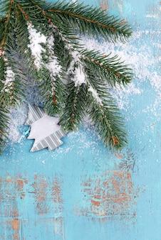 Weihnachtskomposition mit tannenbaum mit spielzeug und schnee auf holzuntergrund