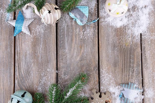 Weihnachtskomposition mit tannenbaum, spielzeug und schnee auf hölzernem hintergrund