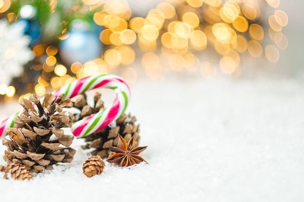 Weihnachtskomposition mit tannenzapfen zuckerstange und anisstern auf dem schnee