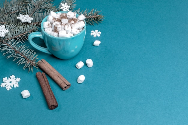 Weihnachtskomposition mit tannenzweigen mit weißen hölzernen schneeflocken und tasse kaffee oder kakao mit marshmallows und zimt auf türkis. gemütlicher urlaub zu hause. weihnachtsdekorationen. kopieren sie platz für text.