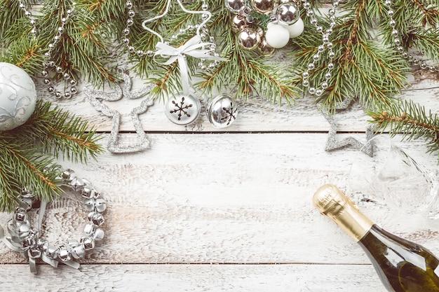 Weihnachtskomposition mit tannenzweigen und weihnachtsdekorationen auf weißem holz