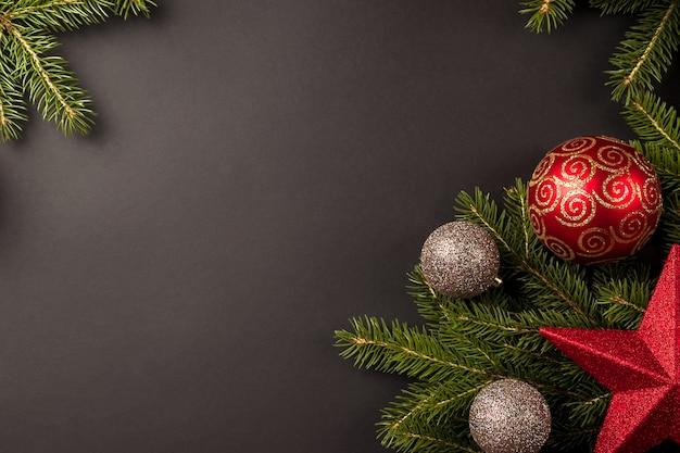 Weihnachtskomposition mit tannenzweigen, weihnachtsschmuck und goldkugeln auf schwarzem hintergrund