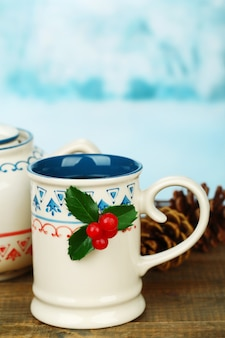 Weihnachtskomposition mit tasse und teekanne heißgetränk auf holztisch