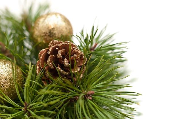 Weihnachtskomposition mit üppigem kiefernzweig, verziert mit goldenen glitzertannenzapfen, glänzenden goldenen kugeln auf weißem hintergrund. vorlage mit kopierplatz für eine grußkarte oder einladung.