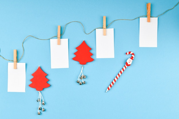 Weihnachtskomposition mit verschiedenen objekten zum schreiben. studio schoss über weihnachtsraum. layout mit leeren blättern. platz zum schreiben. sicht von oben. auf einem blauen raum.