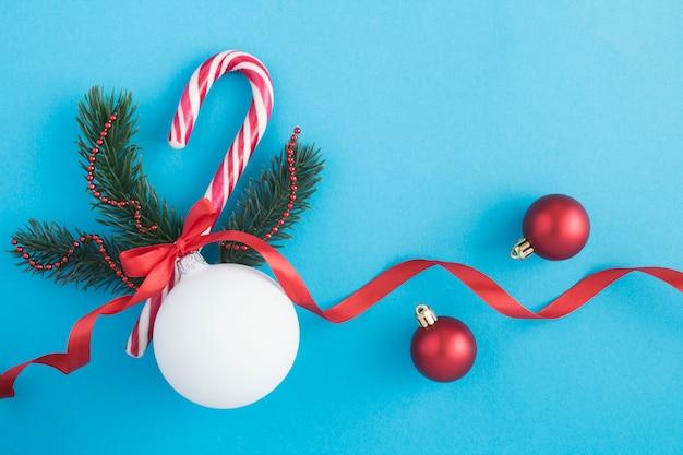 Weihnachtskomposition mit weißer kugel, fichtenzweigen und karamellrohr auf der blauen oberfläche. draufsicht. speicherplatz kopieren.
