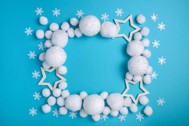 Weihnachtskomposition, quadratischer rahmen der weißen kugeln und glückseligkeit auf einem blauen hintergrund