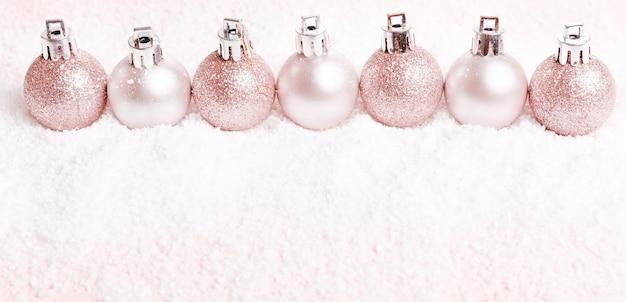 Weihnachtskomposition. rosa und silberne weihnachtskugeln auf schneeweißem hintergrund. flache lage, ansicht von oben, kopienraum