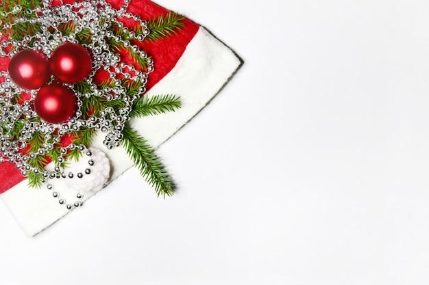 Weihnachtskomposition rote weihnachtskugeln und ein fichtenzweig auf weihnachtsmütze mit glänzenden perlen