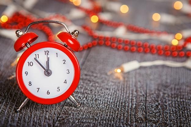 Weihnachtskomposition - roter wecker auf einem strukturierten holzbrett mit lichtern und perlen bokeh