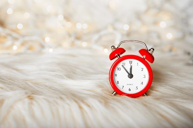Weihnachtskomposition - roter wecker auf einem weißen flauschigen fell mit lichtern und perlen bokeh