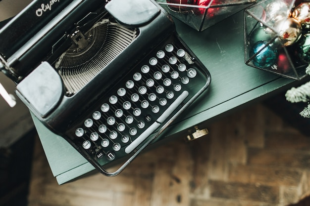 Weihnachtskomposition. schwarze weinlese-retro-schreibmaschine, die auf dem grünen tisch mit weihnachtsspielzeug liegt