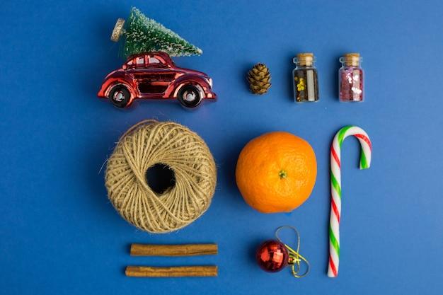 Weihnachtskomposition. spielzeugauto, mandarinen, süßigkeiten auf blauem trendigem hintergrund. festliche kulisse für projekte. flacher lay-stil. ansicht von oben. farbe des jahres.