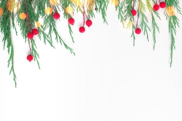 Weihnachtskomposition tannenzweige rote dekorationen auf weißem hintergrund