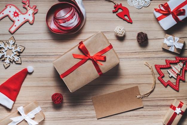 Weihnachtskomposition von weihnachtsbaumspielzeug, bändern und verzierten geschenkboxen auf rustikalem holztisch. leeres bastelpapieretikett zum schreiben von urlaubswünschen