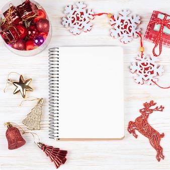 Weihnachtskomposition. weihnachtsdekorationen, girlande, uhr, hirsch, geschenk und leeres notizbuch auf weißem hölzernem hintergrund.