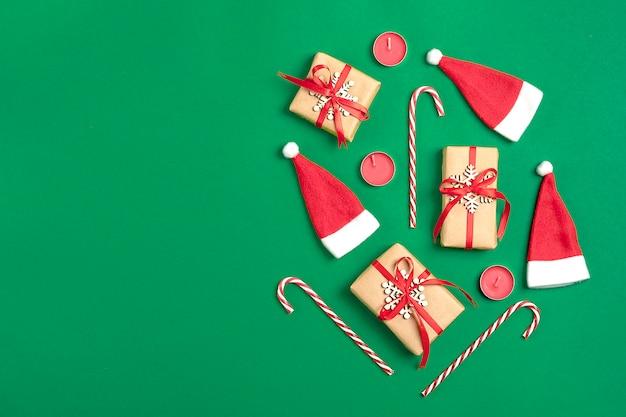 Weihnachtskomposition. weihnachtsdekorationsgeschenke, santa claus-hut, süßigkeit auf grünem backgr