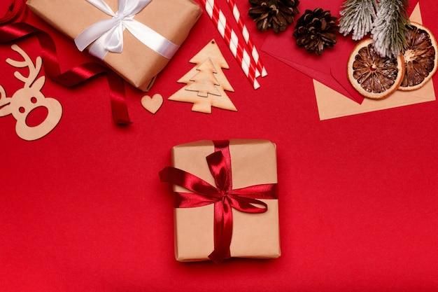 Weihnachtskomposition. weihnachtsgeschenk auf rotem hintergrund draufsicht