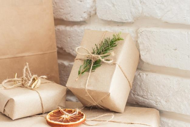 Weihnachtskomposition. weihnachtsgeschenk, gestrickte decke, tannenzapfen, tannenzweige auf weißem holzhintergrund. flache lage, ansicht von oben, kopienraum