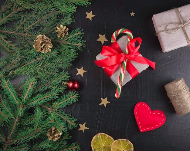 Weihnachtskomposition. weihnachtskegel, weihnachtsbaumzweige, geschenke, festliche dekoration auf schwarzem hintergrund. flache lage, ansicht von oben, mit kopierraum.