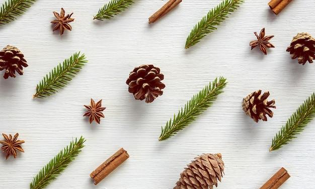 Weihnachtskomposition. wintermuster aus gewürzen, kiefern- und tannenzapfen, zimtstangen, anissternen, tannenzweigen auf weißem holzhintergrund. vintage getönte draufsicht flach legen neues eyar dekor