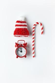 Weihnachtskomposition, zuckerrohrbonbon, kleine analoge uhr, gestreifter hut auf weißer wand. minimaler stil. draufsicht. festliches urlaubskonzept.