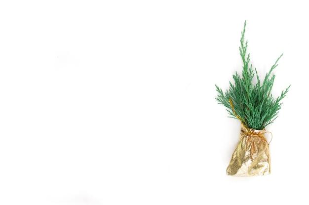 Weihnachtskompositiongoldene tasche mit grünen zypressenzweigen auf weißem hintergrund