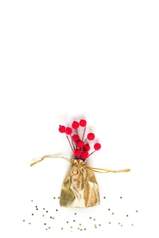Weihnachtskompositiongoldener sack mit roten winterbeeren in zucker auf weißem hintergrund