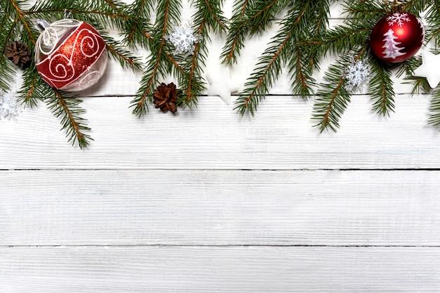 Weihnachtskompositionshintergrund der roten kugeln der fichtenzweige auf einem weißen holz
