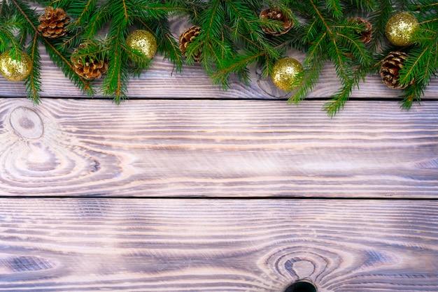 Weihnachtskompositionsspielzeug, geschenke und zweige eines weihnachtsbaumrahmens auf hölzernem hintergrund.