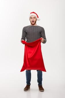 Weihnachtskonzept - attraktiver mann des jungen bartes, der offenen großen beutel sankt für geschenk erregt.