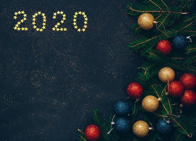 Weihnachtskonzept auf einem schwarzen hintergrund mit spielwaren und grüner tanne.