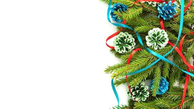 Weihnachtskonzept der tannenzweige und -kegel auf einem isolierten hintergrund.