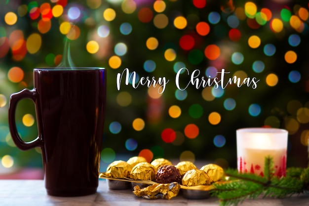 Weihnachtskonzept eine tasse heiße schokolade auf dem hintergrund eines weihnachtsbaumes mit lichtern