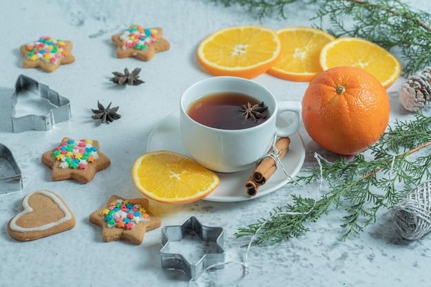 Weihnachtskonzept. frischer tee mit orange und keksen.