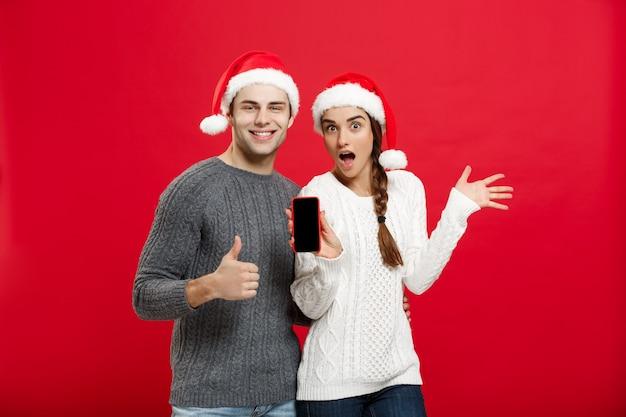 Weihnachtskonzept - glückliches junges paar in den weihnachtspullovern, die schlagaufschlaggeste mit handy zeigen.