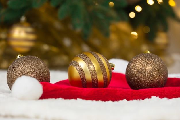 Weihnachtskonzept. goldene kugeln auf weihnachtsmannmütze und weihnachtsbaum