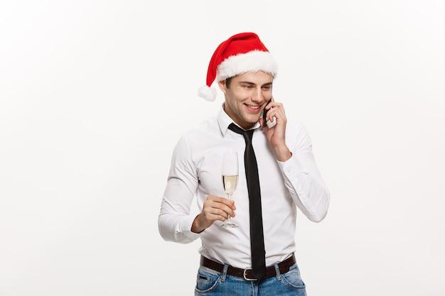 Weihnachtskonzept - hübscher geschäftsmann, der am telefon spricht und ein glas champagner hält, das chirstmas und neujahr feiert.